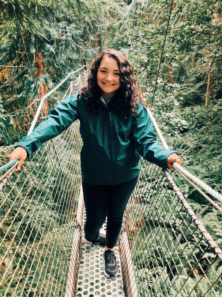 A photo of a light-skinned, female-presenting person with curly brown hair, smiling and standing on a narrow metal bridge surrounded by trees.